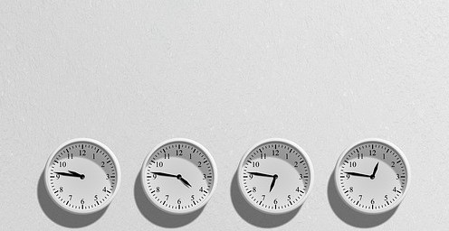 Four White Clocks Showing Different Times